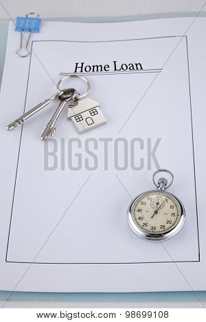 House shaped key chain with keys on top of application form