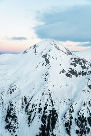 stock photo of pyramid shape  - Pyramid Shaped Mountain Peak Covered in Snow at Sunrise  - JPG