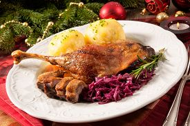foto of canard  - Crusty goose leg with braised red cabbage and dumplings on Christmas decorated table - JPG
