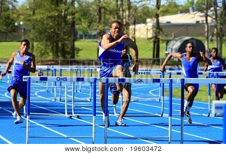 male runners competing during hurdles