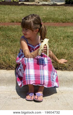 A cute girl sitting on a curb and eating a banana on a hot summer day