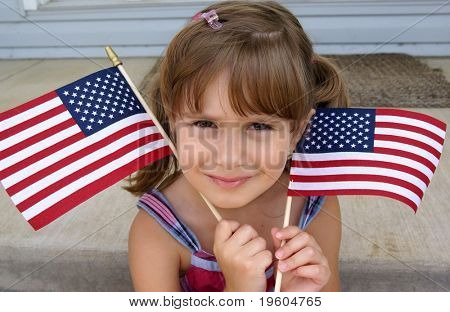 A cute young girl holding two usa flags