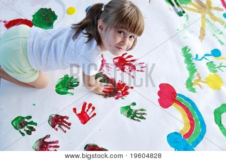 A young girl painting with her hands