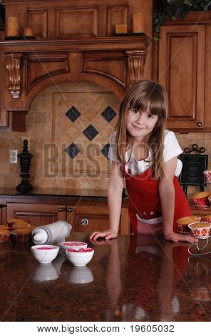 A cute young girl getting ready to ice the cupcakes
