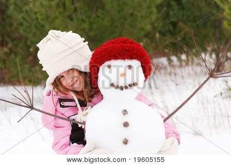 A cute young girl posing with her snowman