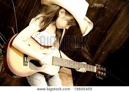 A cute girl playing her guitar, (sepia toned)