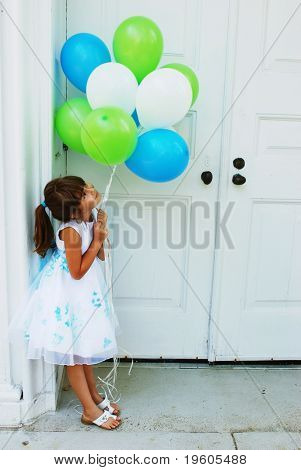 A cute girl holding a bunch of balloons