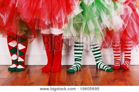 Four little girls wearing christmas socks and tutu's