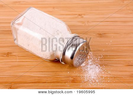 Salt shaker on wooden background