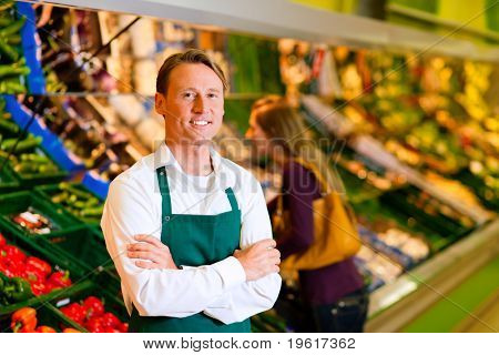 Shop assistant in a supermarket at the vegetable shelf; in the background a woman choosing vegetables