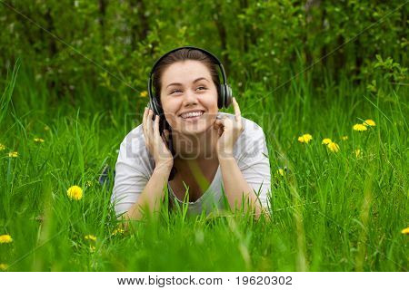 Laughting Woman With Headphones On The Grass