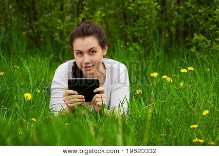 Smiling Girl With Ebook Lying On The Grass