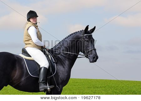 woman and black horse in field