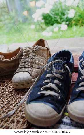 Two Pairs Of Old Sneakers On The Threshold