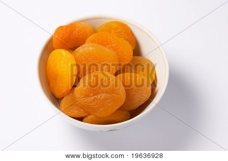 Closeup of cup of dried apricots on white background with light shadow