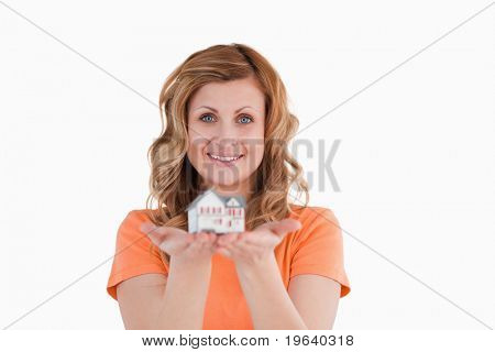 Smiling woman holding an house model on a white background