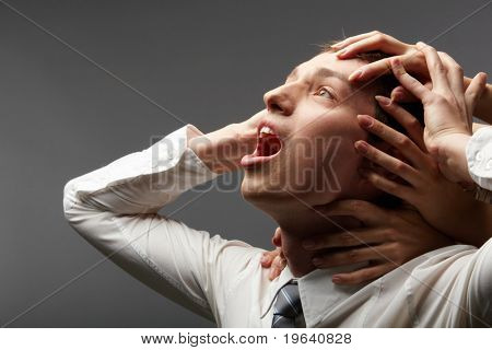 Portrait of a shouting businessman restrained by different hands
