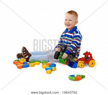Kleiner Junge sitzen unter Spielzeug auf Boden