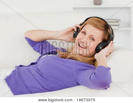 Joyful Red-haired Woman Listening To Music And Enjoying The Moment While Lying On A Sofa