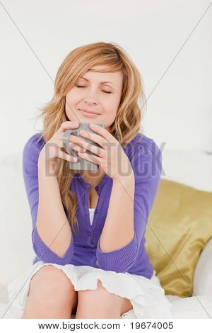 Beautiful Red-haired Woman Holding And Smelling A Cup Of Coffee While Sitting On A Sofa