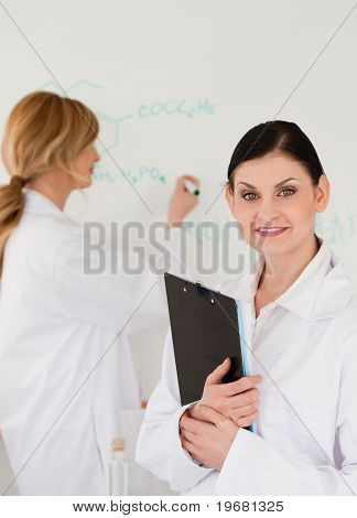Young Scientist Writting A Formula Helped By Her Assistant