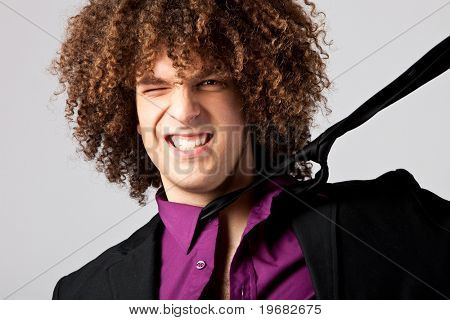 young curly man in shirt having a problem with tie, studio shot