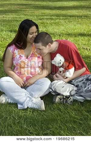 Young man and pregnant woman in a parking holding a teddy bear