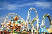 image of amusement  - Amusement park rides with a very blue sky as background - JPG