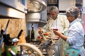 Senior couple preparing food in kitchen at home poster