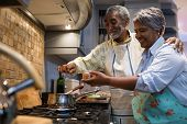 Smiling senior couple preparing food while standing in kitchen at home poster