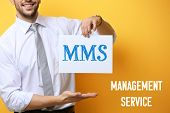 Постер, плакат: Concept of management service Young businessman holding paper with abbreviation MMS on yellow backg