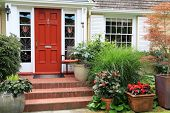 Charming small home with red front door and summer garden containers filled with annual flowers. Pho poster