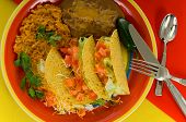 image of mexican food  - Mexican food plaate with tacos bean and rice on brightly colored plate - JPG