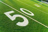 stock photo of football field  - Closeup of 50 yard line on American football field - JPG