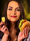 Woman eating hamburger. Portrait of student consume fast food . Girl trying to eat junk. Advertise f poster