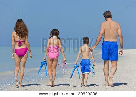 A happy family of mother, father and child, a daughter, walking in swimming costumes on a sunny beach