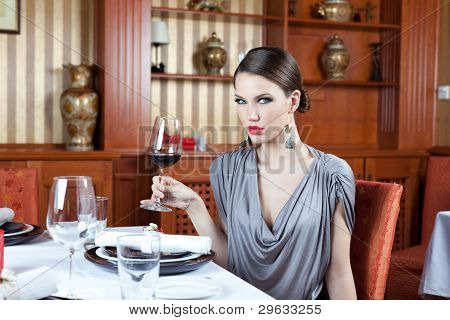 Beautiful Brunette In Restaurant Drinking Wine