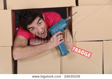 Man with drill amongst boxes