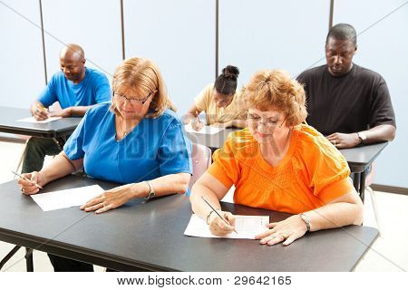 Diverse adult education or college class taking a test.