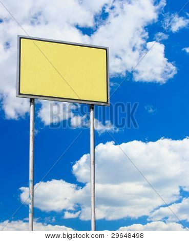 Yellow blank sign against blue sky with clouds