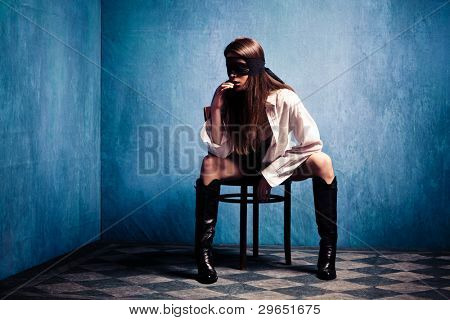 woman with lace over eyes in white shirt and boots sit in old grunge room, small amount of grain added