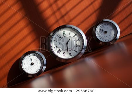 Three clocks on a brown table illuminated by the sun through the blinds.