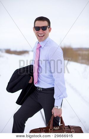 Smiling business man wearing sun-blinkers standing in winter field and holding bag.