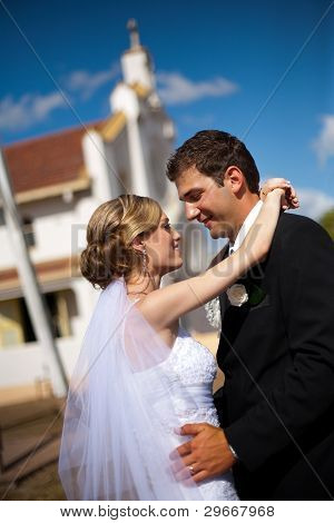 Close Up Of Bride And Groom Hugging In Front Of A Church