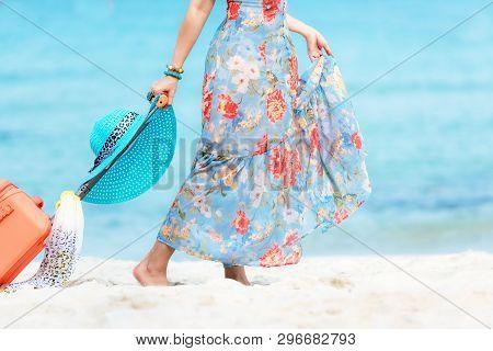poster of Travel Plan. Hand Women Traveler Holding Orange Luggage Walking On The Beach. Traveler And Tourism P