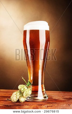beer in glass and green hop on wooden table on brown background
