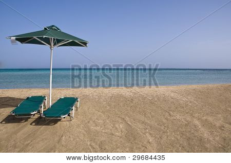 Sunny Beach With Umbrella And Beach Chairs