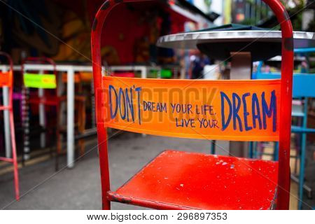 poster of don't dream your life, live your dream - message on the back of a red chair