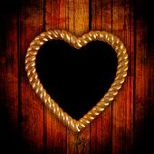 gold picture frame in shape of heart on grunge background