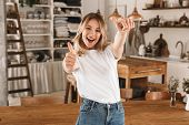 Portrait of happy blond girl 20s wearing casual t-shirt smiling and showing thumb up while standing  poster